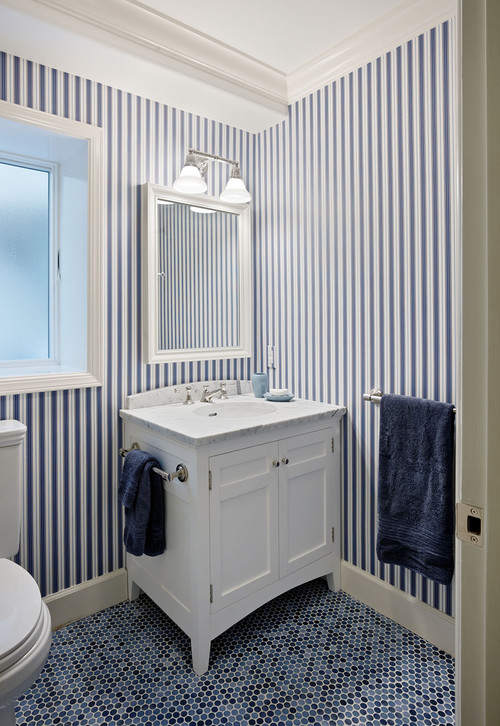 striped navy and white wallpaper paired with navy penny tiles on the floor make up a chic ambience