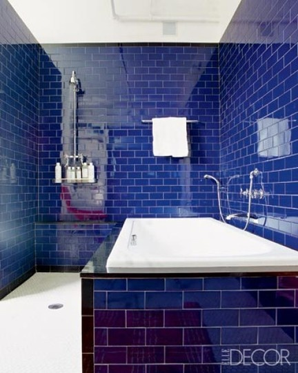 bold and glossy navy tiles with white grout plus a white bathtub for a bright and chic look