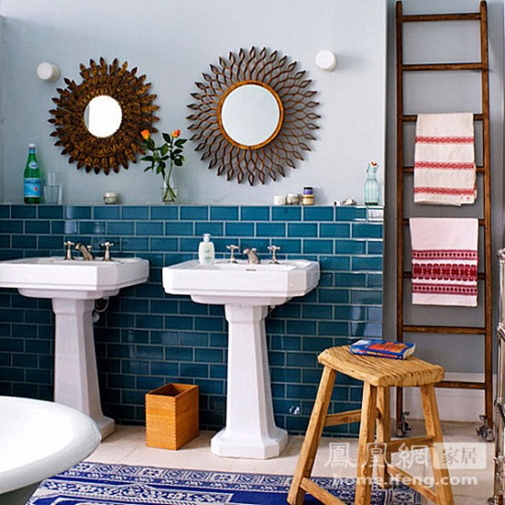 bright blue tiles on the wall and a navy and white printed rug add color to the eclectic bathroom