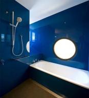 a minimalist and sleek bright blue bathroom plus a gold floor and a white tub