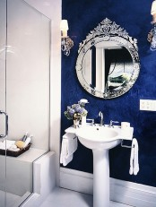 a navy textural wall and a mirror in a refined and chic frame adds a luxurious touch to the space
