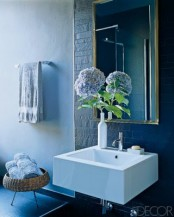 matte navy tiles and a navy tile floor for a chic and bold bathroom plus light blue towels