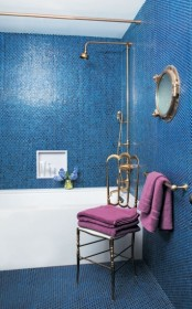 bright blue penny tiles paired with brass fixtures and a porthole create a cool bold look with a nautical feel