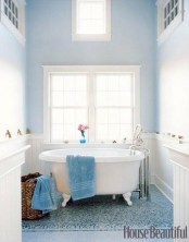 a light blue bathroom and a bright blue tile wall is refreshed with white touches and furniture