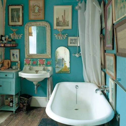 bright turquoise walls with lots of artworks for a vintage and eclectic bathing space