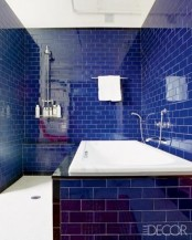 a very bright and glossy navy tile bathroom accented with white grout plus metallic fixtures