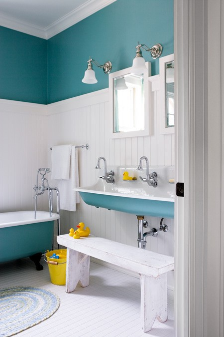 a turquoise wall, a clawfoot bathtub and a sink for a vintage and chic bathroom
