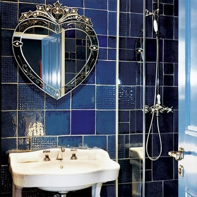 mismatching blue and navy tiles on the wall and a refined heart-shaped mirror for a luxurious space