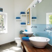 a sleek light blue half wall and bright blue towels for a contemporary bathroom