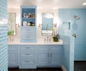 a serenity blue bathroom done with tiles with white grout and a vintage storage unit and vanity