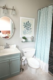 an aqua vanity and a printed aqua and white curtain for a subtle touch of color