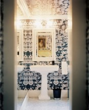 eye-catchy navy and white printed wallpaper on the walls and ceiling plus a white floor