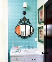 bright turquoise tiles to accent the white vanity and sink plus a mirror in a vintage frame
