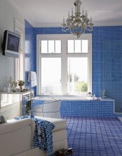 a bright blue tile bathroom is a very bold idea, a matching rug with a vindwopane print