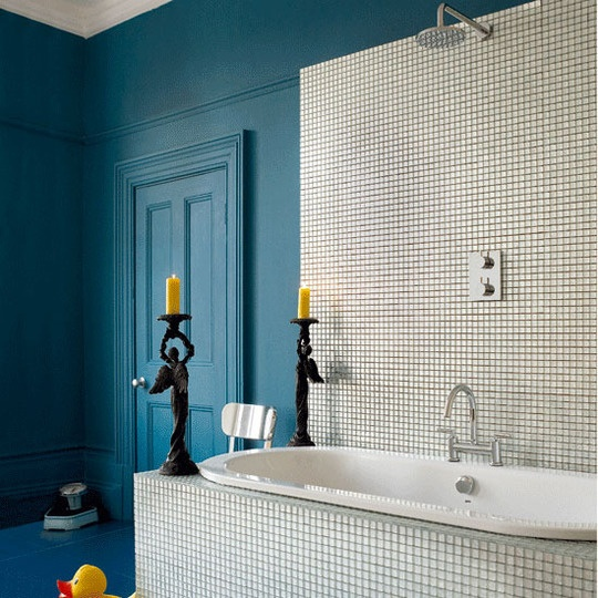 a bright blue bathroom with a bathtub accented with neutral tiles and a backsplash of them