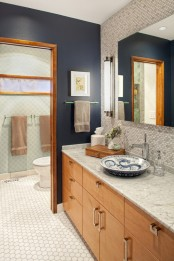 navy walls paired with marble penny tiles create a chic and bold modern look, light-colored wood adds coziness