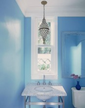 a bright blue bathroom refreshed with white touches and a crystal pendant lamp