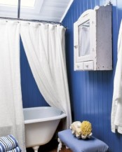 a navy beadboard clad bathroom with much white and matching furniture for a bold look