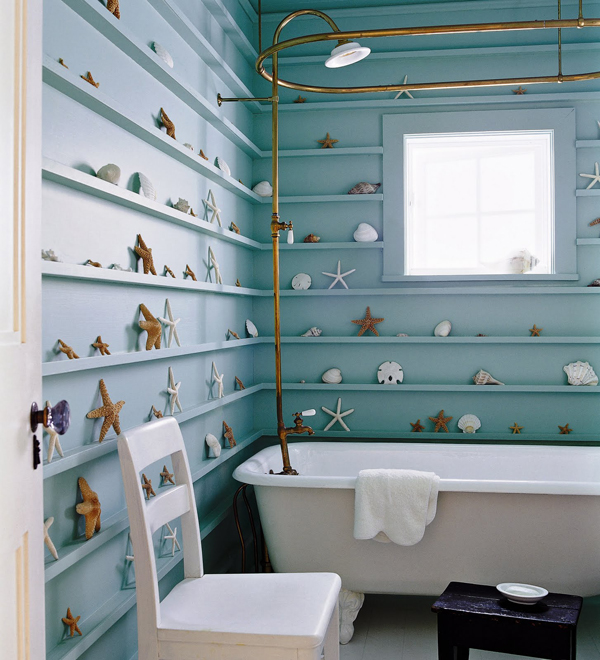 turquoise walls with ledges to display various seashells and starfish and white furniture and a tub