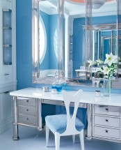 a refined bathroom with light blue tiles, a mirror vanity plus a storage unit