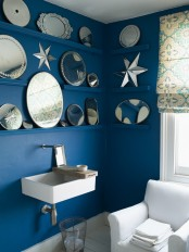 bold blue walls with ledges to display artworks and decorative plates, white elements for a bright feel