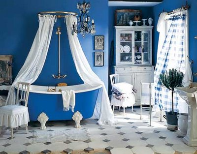a bright blue bathroom with a bold clawfoot bathtub and white furniture and textiles