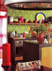 a colorful kitchen with boho touches – brown furniture, printed wallpaper, touches of red and boho prints looks unusual