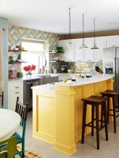 a bright kitchen with white cabinetry, a colorful tile backsplash and a bold yellow kitchen island is a fun and cool space with a beachy feel