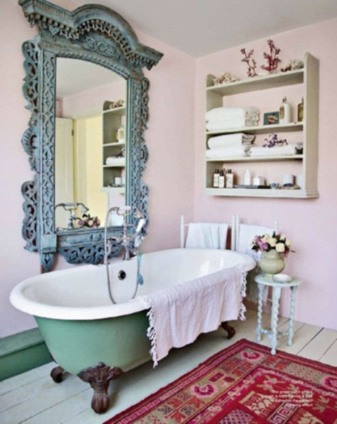 a pink bathroom with a green clawfoot tub, boho rugs, a large ornate mirror in a blue frame and a shelf