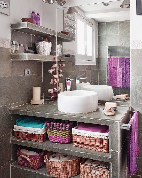 a grey bathroom clad with sotne like tiles and with bright towels and other textiles