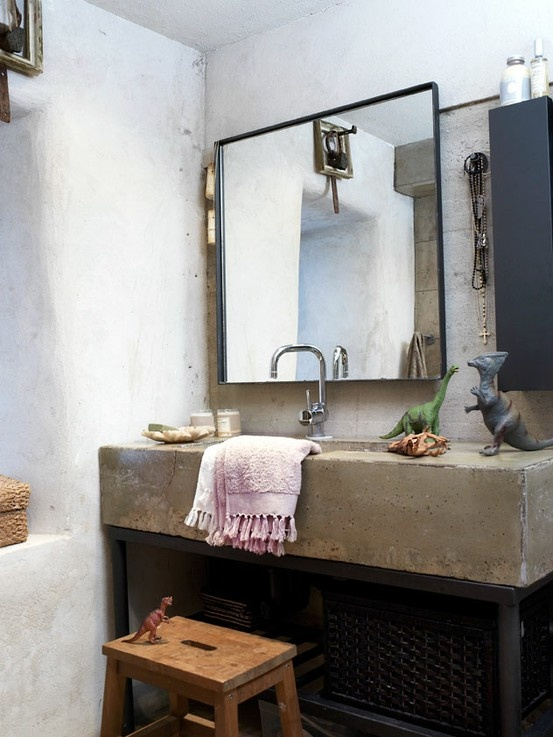 a wabi sabi bathroom with a concrete sink, a large mirror, a wooden stool, bright towels and dinosaurs