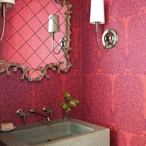 a bright pink and purple patterned space with a concrete sink and a gorgeous ornate mirror