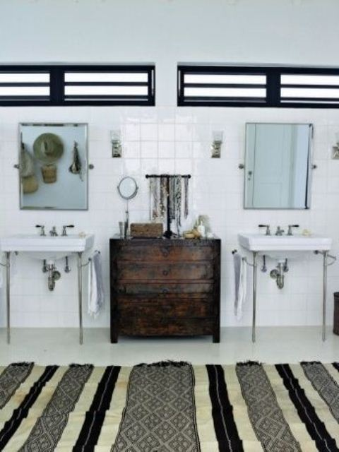 a monochromatic bathroom with a striped rug, a dark stained dresser and straw hats