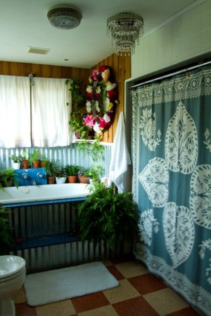 a relaxed boho bathroom with a boho blanket on the wall, a metal clad tub, potted greenery and blooms and checked tiles