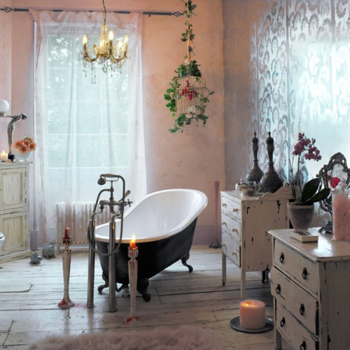a romantic vintage and shabby chic bathroom with shabby dressers, a vintage clawfoot tub, candles, a cage and a crystal chandelier