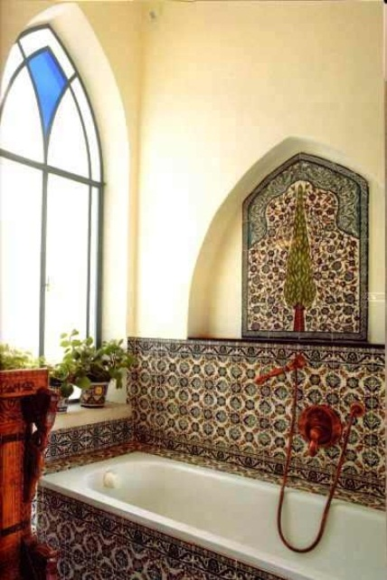a bright Moroccan space with Moroccan tiles, a mosaic window, potted greenery and dark copper hardware