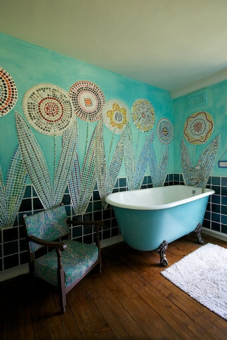 a creative bathroom with turquoise walls done with mosaic florals for a free-spirited feel, a bright clawfoot tub and a vintage chair