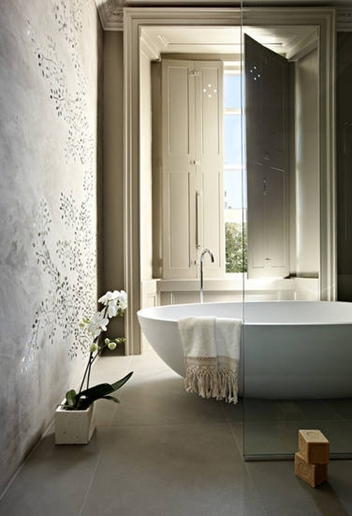 a neutral bathroom with plaster walls, a large tub and handmade soaps right on the floor