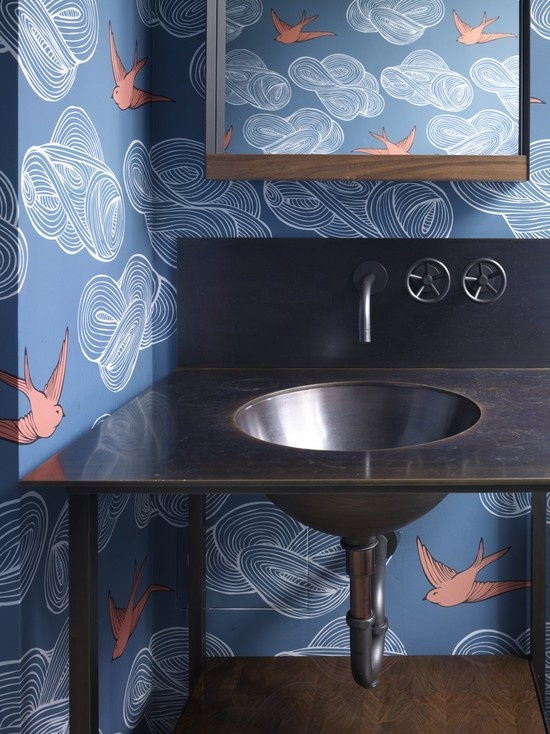 a bathroom done with blue wallpaper and coral birds, a stained vanity and a dark metal sink