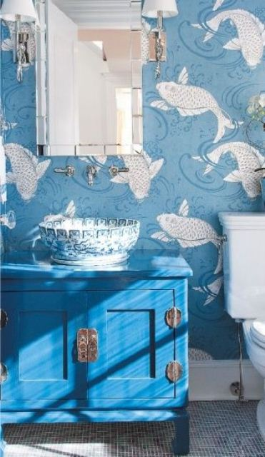 a blue bathroom with fish print wallpaper, a bright blue vanity, a painted vessel sink and a chic mirror