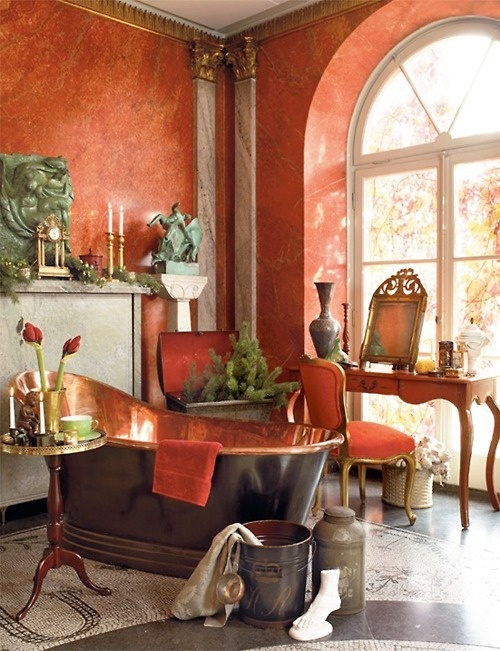 an elegant vintage bathroom with red plaster walls, a black and copper tub, chic sculptures and a vintage console table