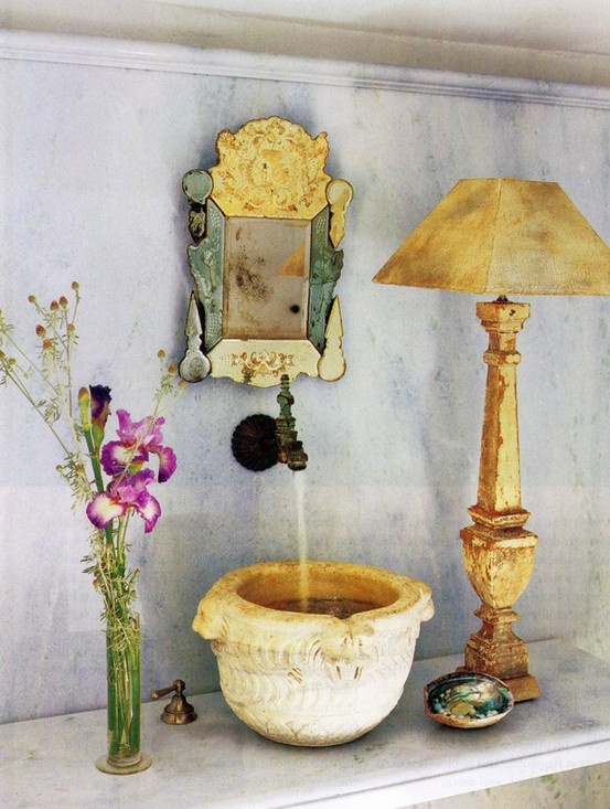 a unique bathing space with a stone carved sink, an ornate mirror, a chic lamp and a floral arrangement