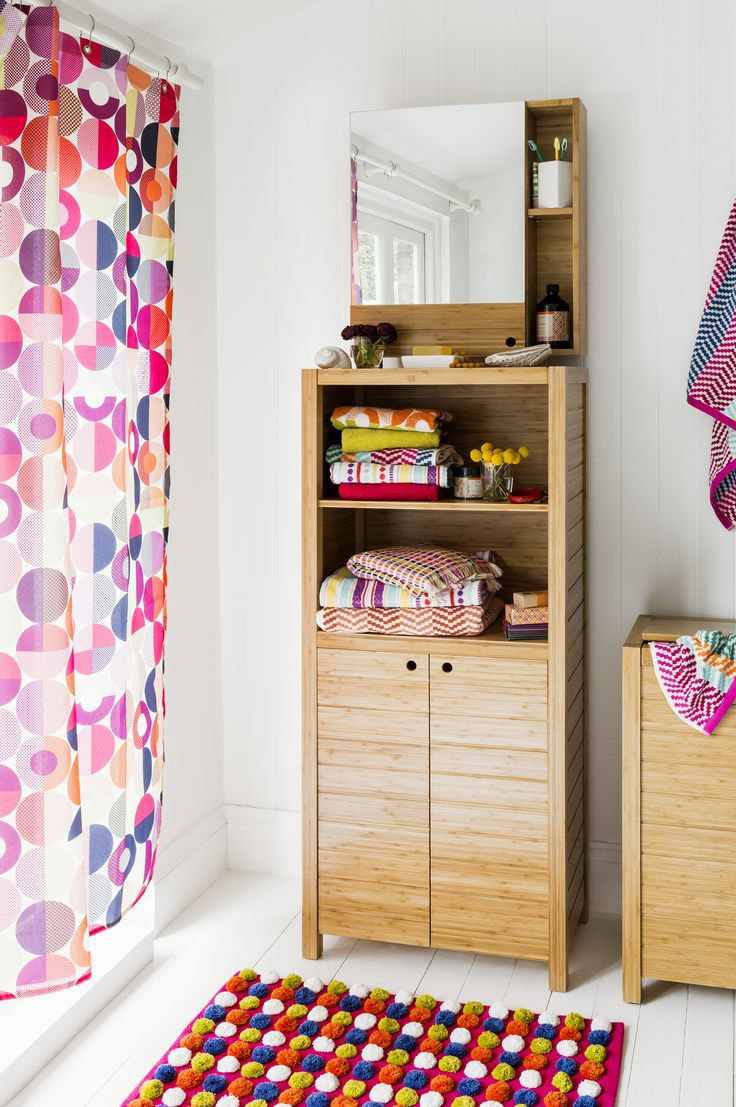 a neutral bathroom with light wooden furniture, a colorful curtain and a rug plus bright towels