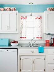 a bright blue kitchen with white cabinetry, bold blue accessories and printed red touches is a vivacious space