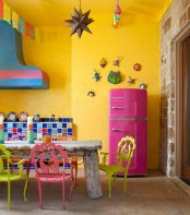 a colorful space with yellow walls, a colorful tile backsplash, a whitewashed rough wood table, yellow and pink chairs and colorful decorations plus a pink fridge