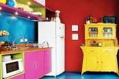 a crazy colorful kitchen with a bold blue and bold red wall, a bright yellow buffet, hot pink cabinets and niches in green, with lights