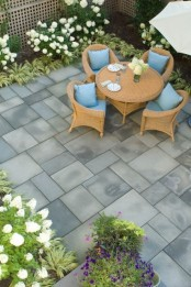 a laconic terrace clad with tiles, with growing greenery and blooms, a wicker dining set and an umbrella over it