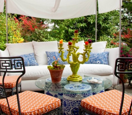 a colorful spring terrace with forged furniture, white and blue textiles and coral chairs, a tent over the space and blooms