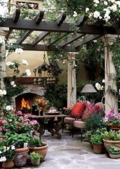 a bright modern spring terrace with greenery and blooms all around, with a heavy wooden table, neutral chairs and lamps and chandeliers