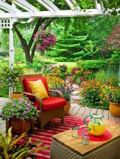 a colorful spring terrace with a boho feel, with wicker furniture, bright blooms and greenery and bold pillows and upholstery